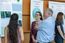 Students discuss their poster with faculty